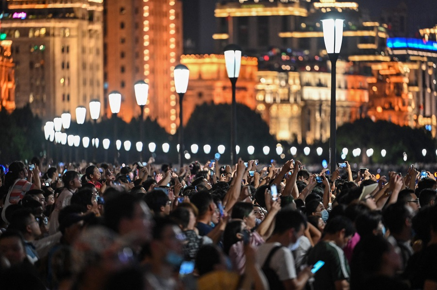 Spectators look at a light show on the Bund promenade in Shanghai, China, on 1 July 2021, as the country marks the 100th anniversary of the founding of China's Communist Party. (Hector Retamal/AFP)