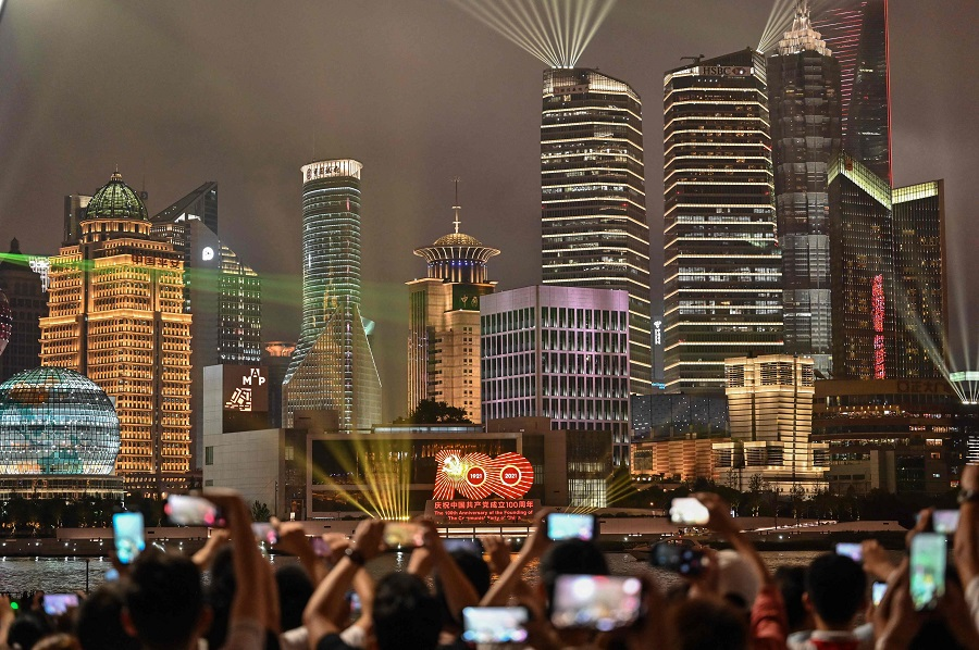 Spectators look at a light show on the Bund promenade in Shanghai, China, on 1 July 2021, as the country marks the 100th anniversary of the founding of the Communist Party of China. (Hector Retamal/AFP)