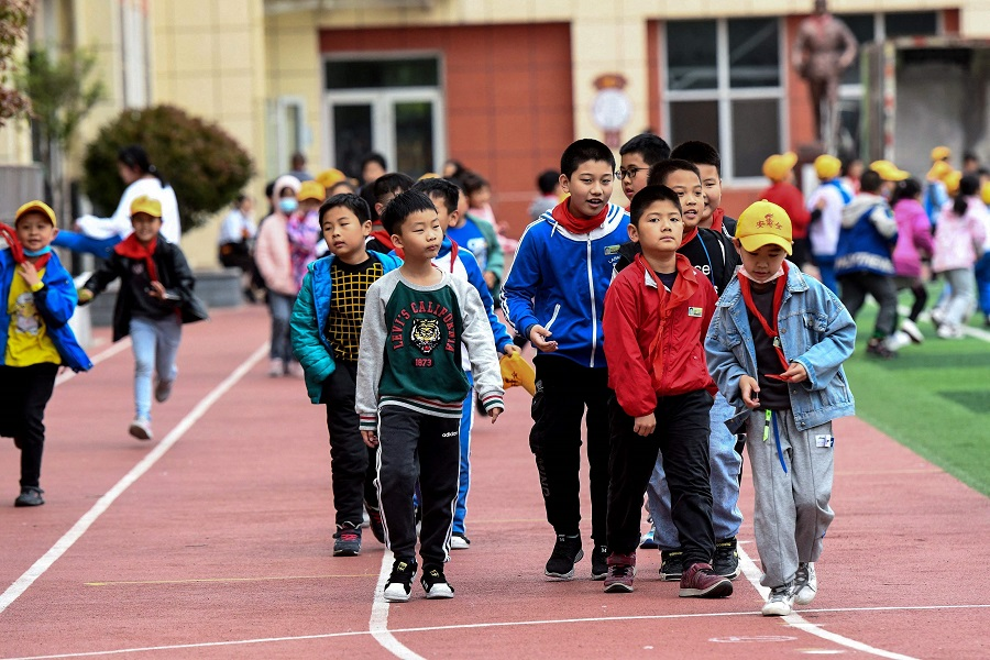 Students walk along a playground at an elementary school in Qingdao, Shandong province, China on 11 May 2021. (STR/AFP)