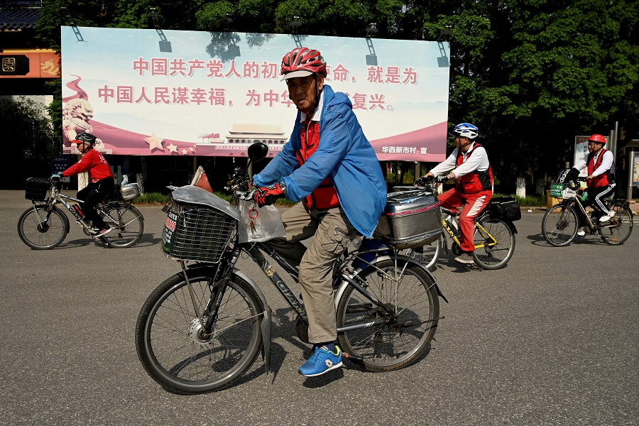 """This photo taken on 22 May 2021 shows people cycling in front of a poster that reads """"The original intention and mission of the Chinese Communists is to seek happiness for the Chinese people and rejuvenation for the nation"""", along a street in Huaxi village, Jiangsu province, China. (Noel Celis/AFP)"""