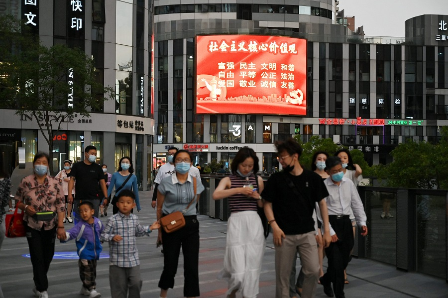 """In this photo taken on 2 June 2021, a large screen shows a propaganda slogan which reads """"Socialist core values; prosperity, democracy, civility, harmony, freedom, equality, justice, the rule of law, patriotism, dedication, integrity, friendship"""", at a shopping mall in Beijing, China. (Greg Baker/AFP)"""