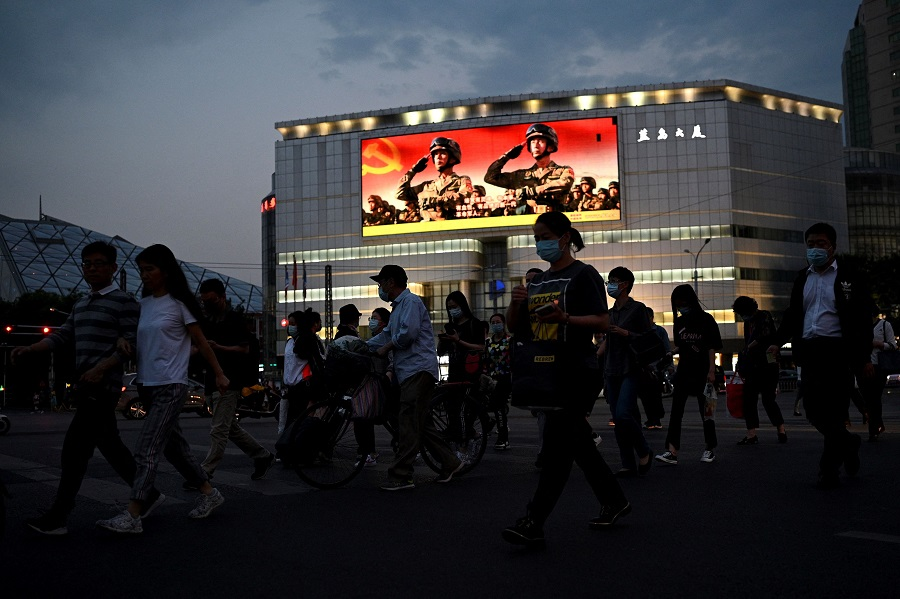This photo taken on 18 May 2021 shows people walking along a street as military propaganda is displayed on a giant screen in Beijing, China. (Noel Celis/AFP)