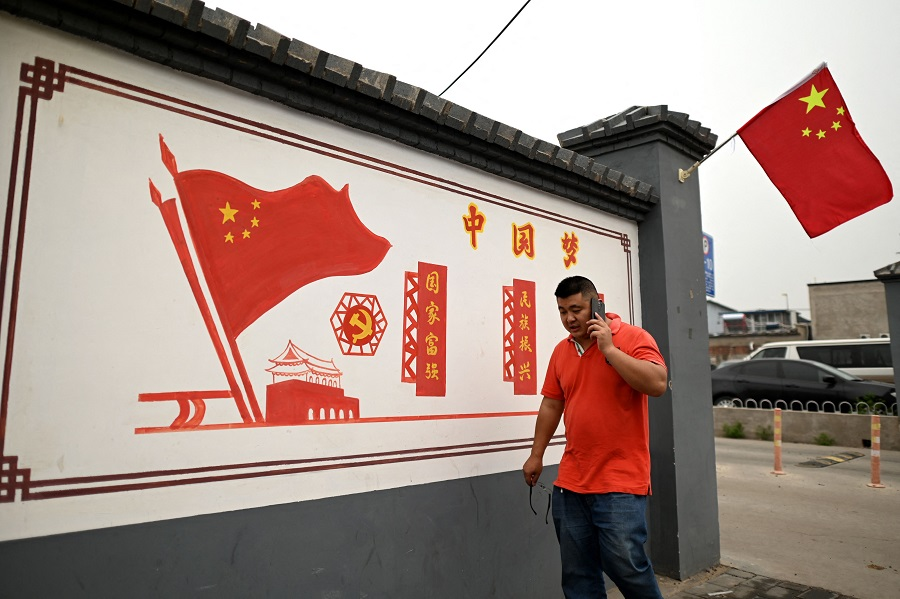 """This photo taken on 9 June 2021 shows a man walking past a propaganda mural that reads """"Chinese Dream: Make the country prosperous and strong, rejuvenate the nation"""" along a street in Beijing, China. (Noel Celis/AFP)"""