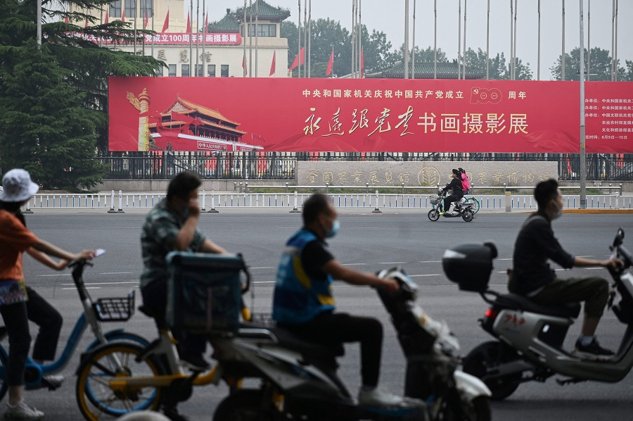 """In this photo taken on 9 June 2021, people ride past a propaganda slogan which reads """"Follow the Party Forever"""", outside an exhibition of calligraphy, painting and photography celebrating the 100th anniversary of the founding of the Communist Party, at an exhibition centre in Beijing, China. (Greg Baker/AFP)"""