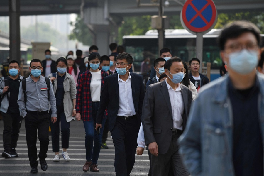 Commuters cross a street during the morning rush hour in Beijing, China, on 11 May 2021. (Greg Baker/AFP)