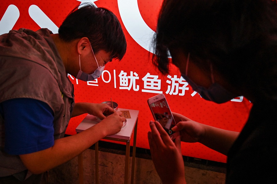 This photo taken on 12 October 2021 shows a customer cutting a dalgona, a crisp sugar candy featured in the Netflix series Squid Game, in Shanghai, China. (Hector Retamal/AFP)