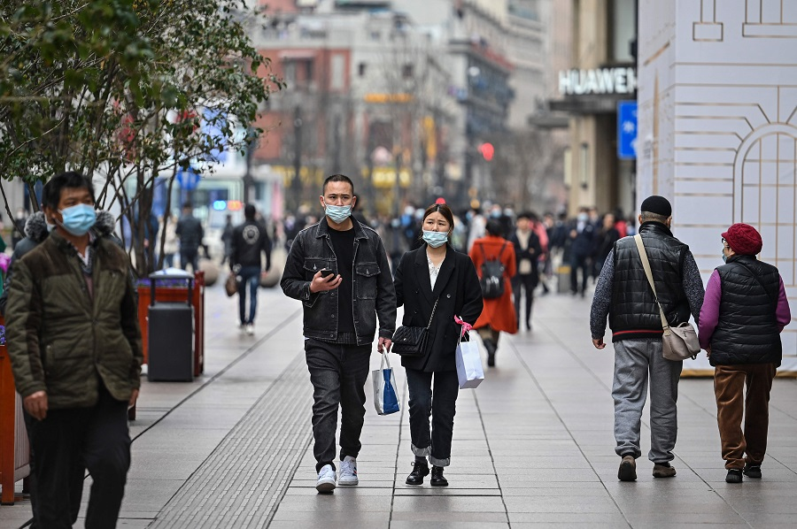 In this photo taken on 5 March 2021, a couple walks on a shopping street in Shanghai, China. (Hector Retamal/AFP)