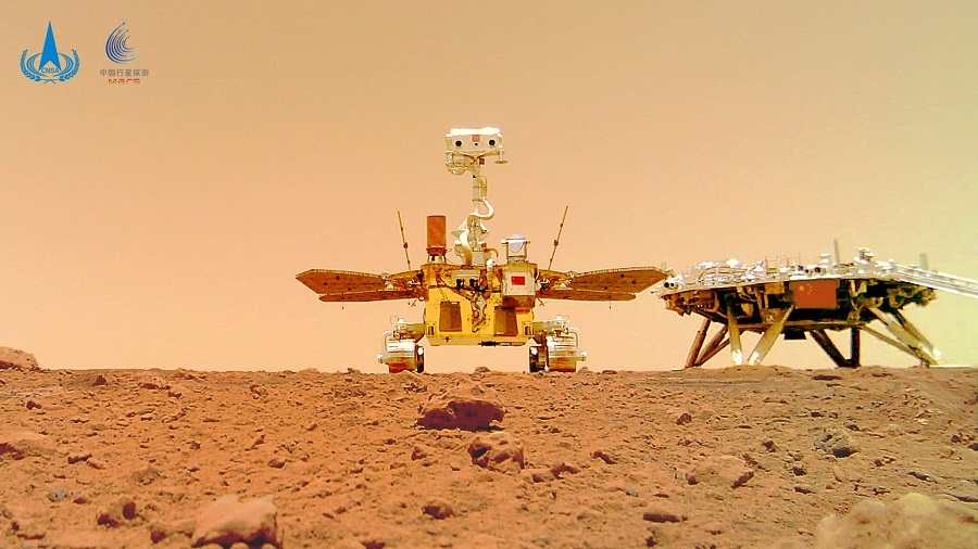 This undated handout photograph released on 11 June 2021 by the China National Space Administration (CNSA) shows an image taken by a camera released from China's Zhurong Mars rover showing the rover (left) and the landing platform on the surface of Mars. (Handout/China National Space Administration (CNSA)/AFP)
