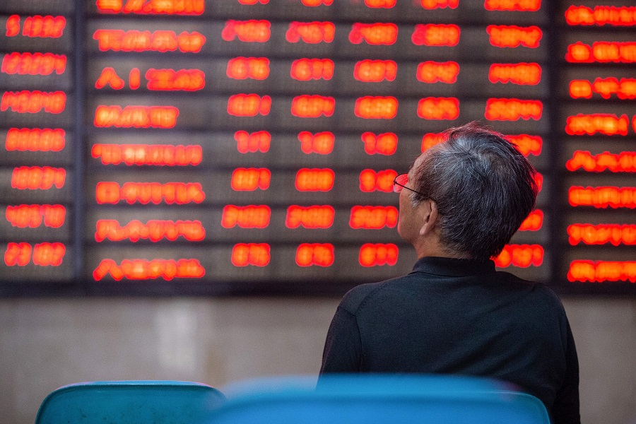 An investor looks at screens showing stock market movements at a securities company in Nanjing, China, on 6 July 2020. (STR/AFP)
