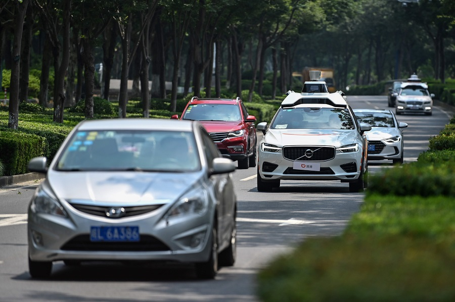This photo taken on 22 July 2020 shows a Didi Chuxing autonomous taxi (centre) during a pilot test drive on the streets of Shanghai. (Hector Retamal/AFP)