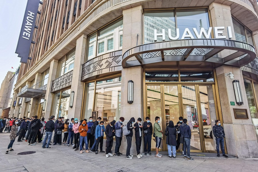 People wearing masks wait in line in front of Huawei's flagship store for pre-sales of the newly launched Huawei Mate 40 mobile phone series in Shanghai on 23 October 2020. (STR/AFP)