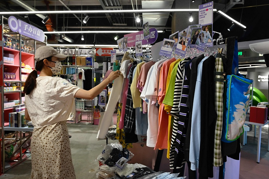 A customer browses clothing similar to those worn by celebrity idols at a fan merchandise store at a shopping mall in Beijing, China, on 2 September 2021. (Jade Gao/AFP)