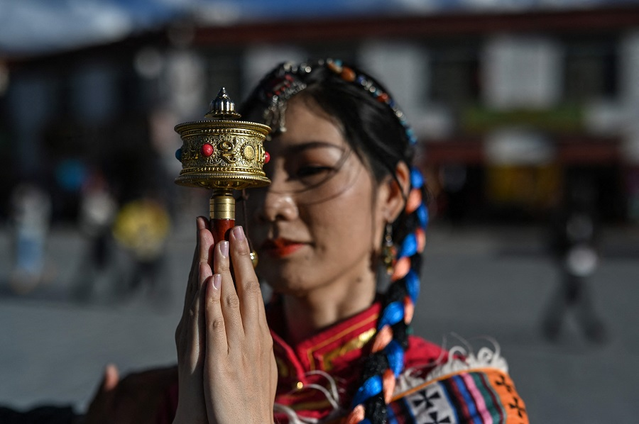 This photograph taken on 1 June 2021 during a government organised media tour shows a tourist posing for a photographer next to Jokhang Temple in the regional capital Lhasa, in China's Tibet Autonomous Region. (Hector Retamal/AFP)