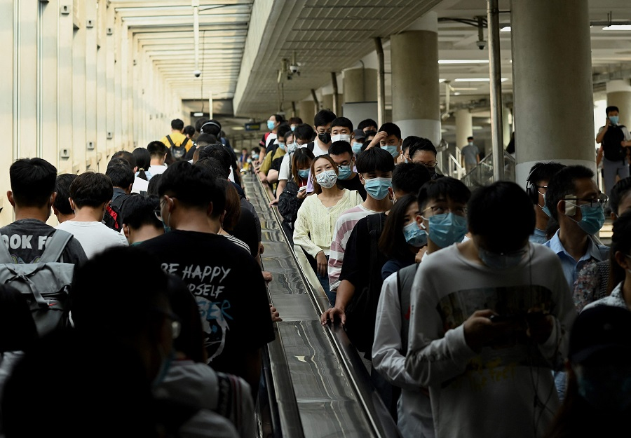 People ride escalators in and out of the subway in Beijing, China, on 9 August 2021. (Noel Celis/AFP)