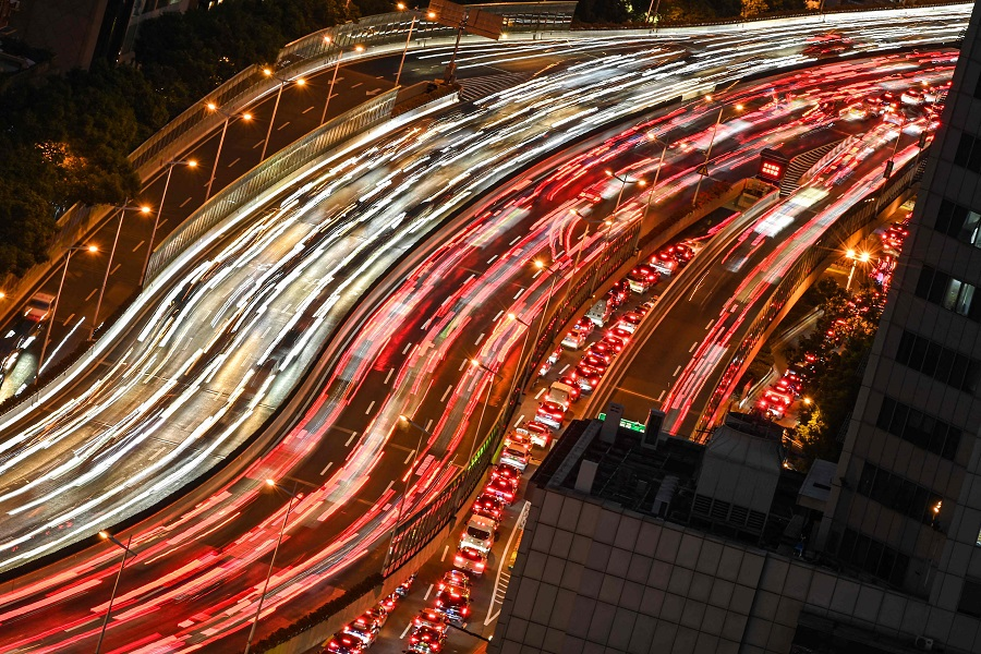 A slow shutter speed photograph shows commuters on vehicles making their way along a busy highway in Shanghai, China, on 7 September 2021. (Hector Retamal/AFP)