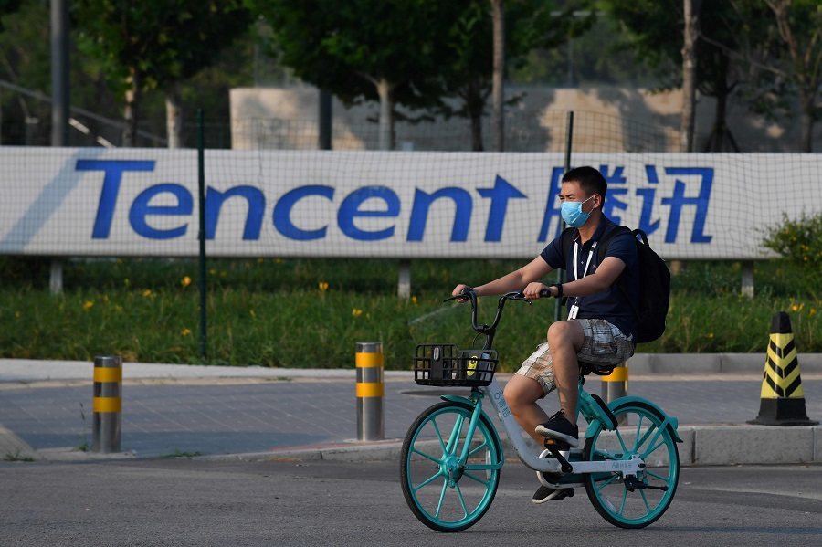 A man walks past a sign for Tencent, the parent company of Chinese social media giant WeChat, outside the Tencent headquarters in Beijing on 7 August 2020. (Greg Baker/AFP)