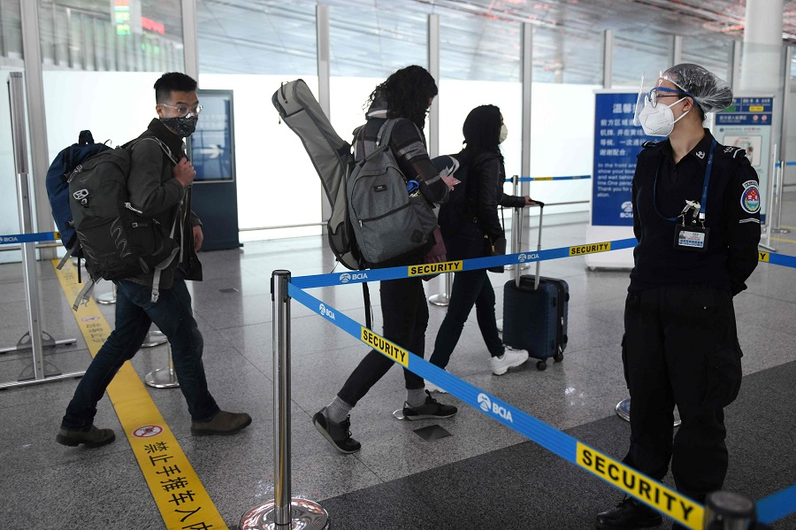 Wall Street Journal reporters Stu Woo (left), Julie Wernau (centre) and Stephanie Yang head into the security area at Beijing Capital Airport on 28 March 2020 after being forced to leave China. (Greg Baker/AFP)