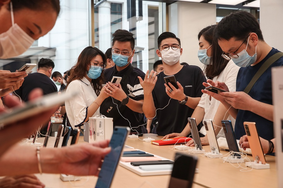 Customers look at Huawei smartphones at a newly-opened Huawei global flagship store in Shanghai on 24 June 2020. (STR/AFP)