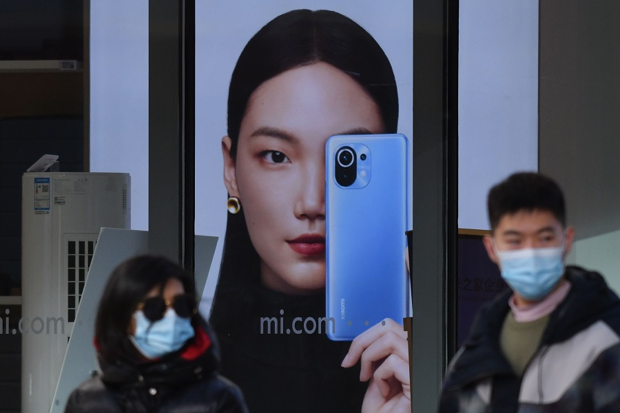 People walk past a Xiaomi store in Beijing on 15 January 2021, as shares in the company collapsed on January 15 after the United States blacklisted the smartphone giant and a host of other Chinese firms. (Greg Baker/AFP)