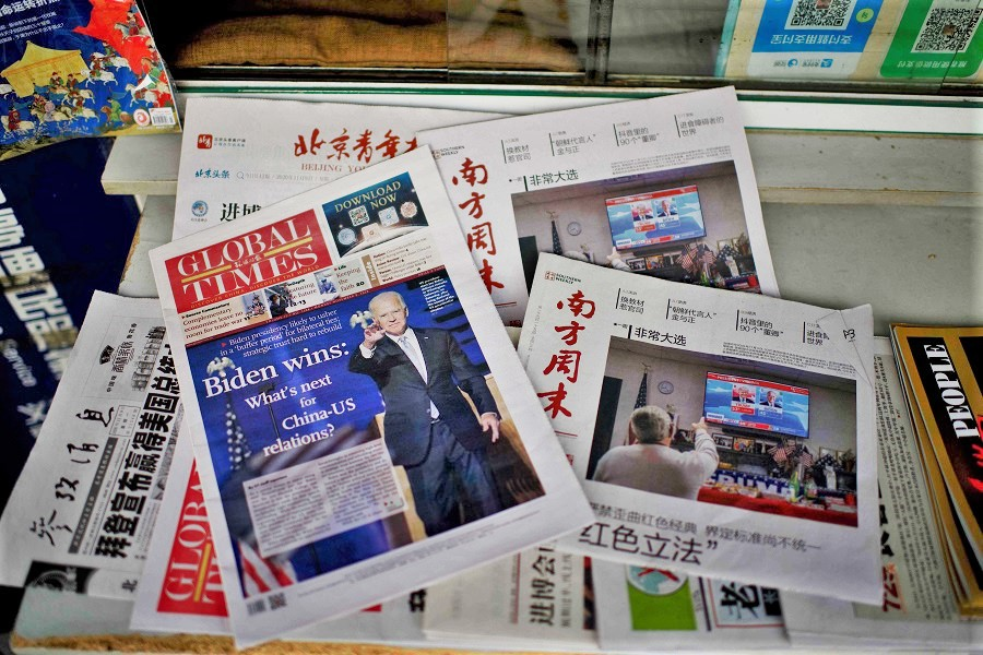 Newspaper front pages lead with the victory of Joe Biden in the US presidential election, at a news stand in Beijing on 9 November 2020. (Noel Celis/AFP)