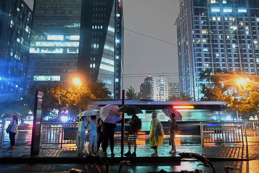 People wait for the bus as it rains in Beijing, China on 23 August 2021. (Noel Celis/AFP)