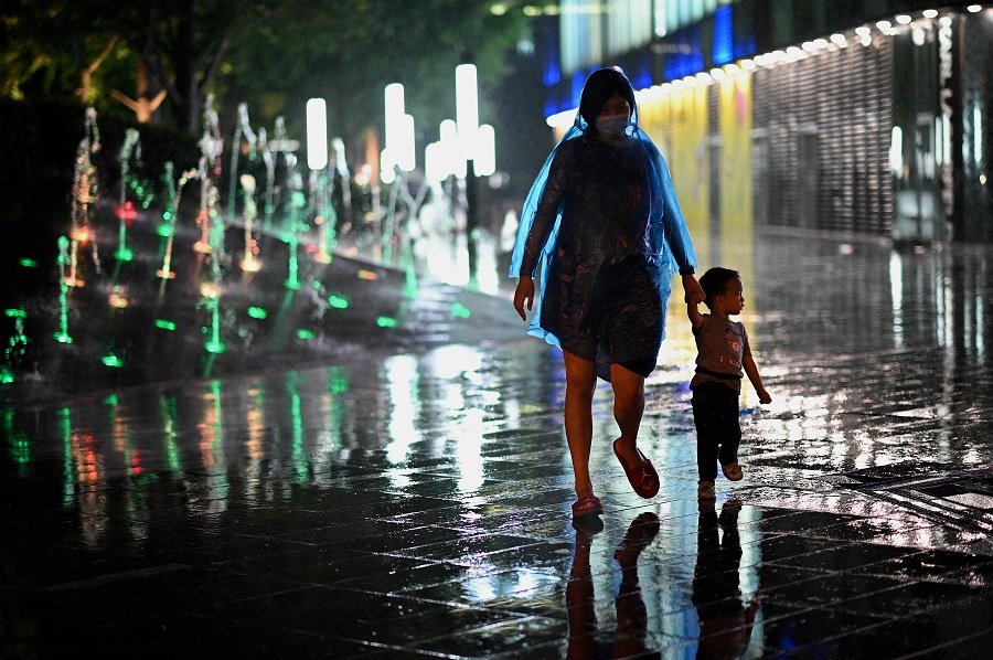 A woman and a child walk past a mall as it rains in Beijing, China, on 23 August 2021. (Noel Celis/AFP)