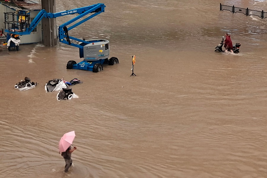 This photo taken on 20 July 2021 shows people wading through flood waters along a street following heavy rains in Zhengzhou, Henan province,China. (STR/AFP)