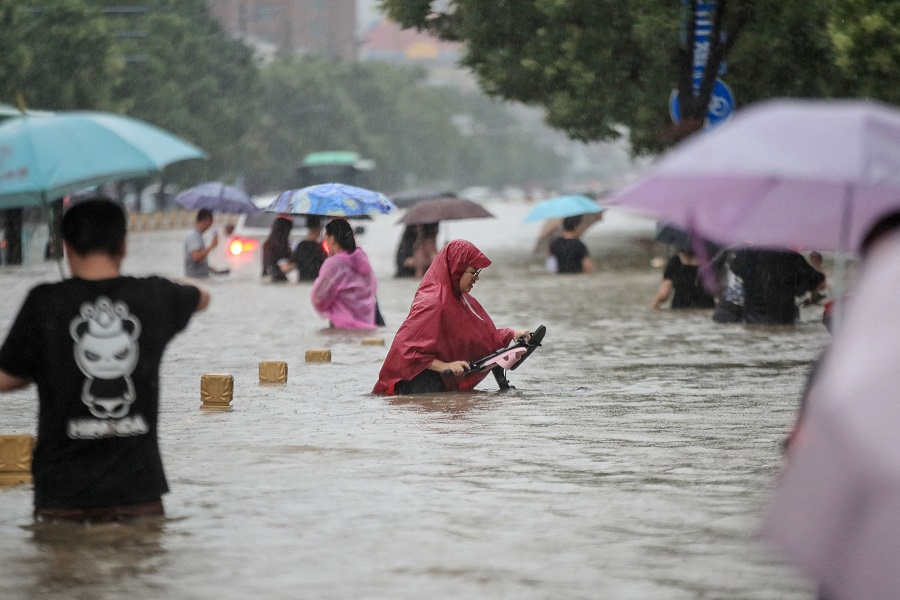 This photo taken on 20 July 2021 shows people wading through flood waters along a street following heavy rains in Zhengzhou, Henan province, China. (STR/AFP)