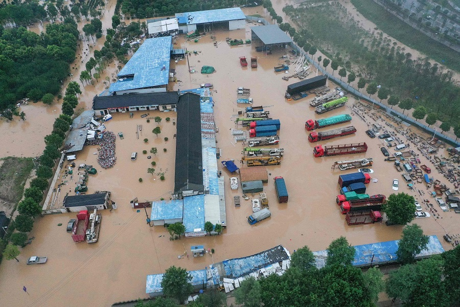 This aerial photo taken on 7 July 2020 shows inundated buildings and vehicles after heavy rain caused flooding in Shexian county, Huangshan city, Anhui province, China. (STR/AFP)