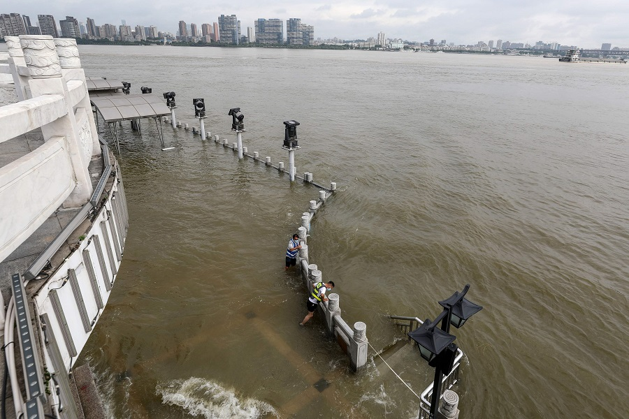 Workers monitor the flood situation along the overflowing Yangtze River in Wuhan, Hubei, China, on 8 July 2020. (STR/AFP)