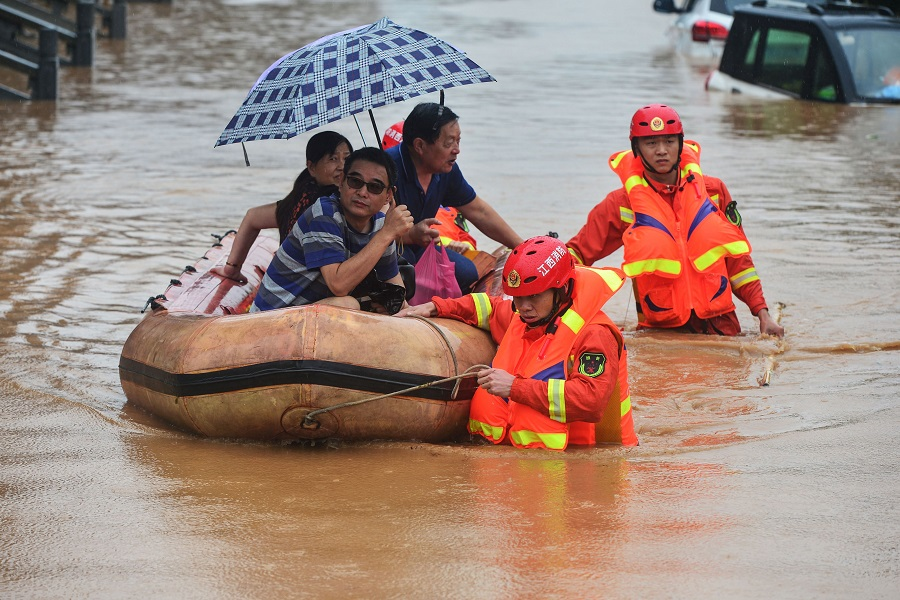 Rescuers evacuate flood-affected residents following heavy rain in Jiujiang, Jiangxi province on 8 July 2020. (STR/AFP)