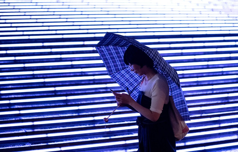 A woman uses her mobile phone at a mall in Beijing on 18 August 2020. (Noel Celis/AFP)