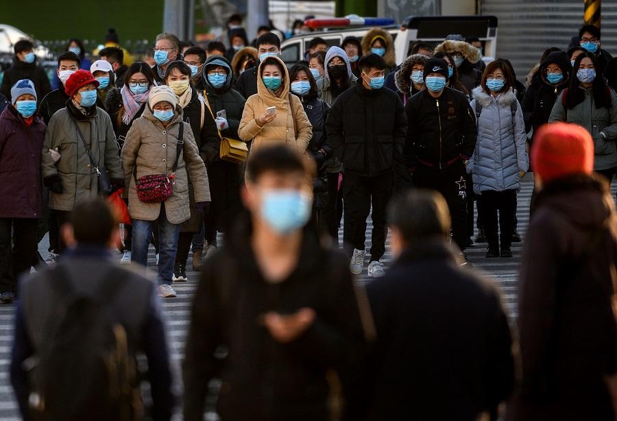 People wearing face masks walk along a street during a rush hour in Bejing on 16 December 2020. (Noel Celis/AFP)