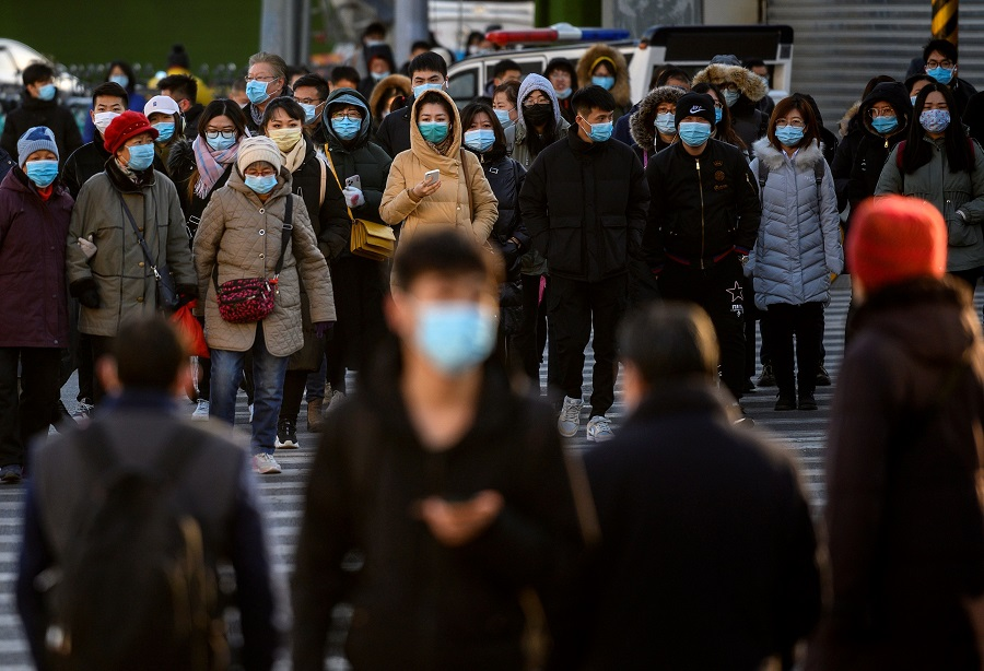 People wearing face masks walk along a street during a rush hour in Bejing on 16 December 2020. (Noel Celis/AFP)