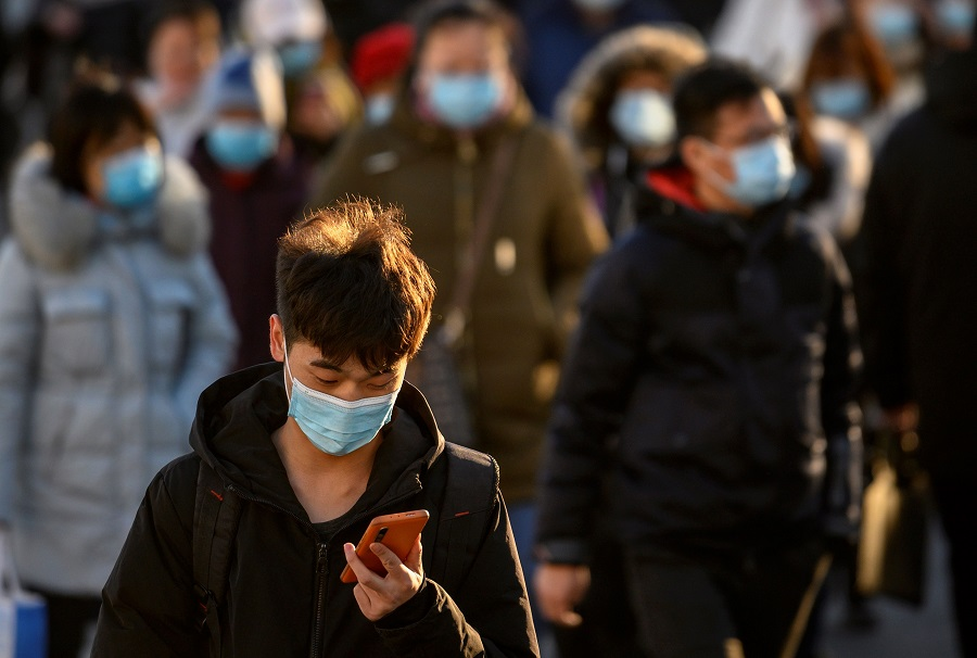 People wearing face masks walk along a street during a rush hour in Beijing on 16 December 2020. (Noel Celis/AFP)