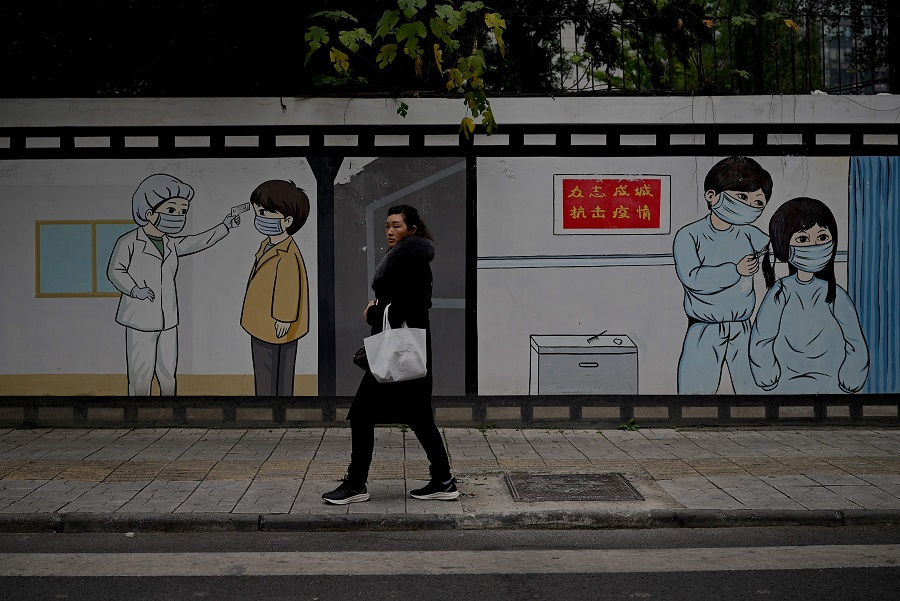A woman walks along a street in Chengdu, Sichuan province, 27 November 2020. (Noel Celis/AFP)