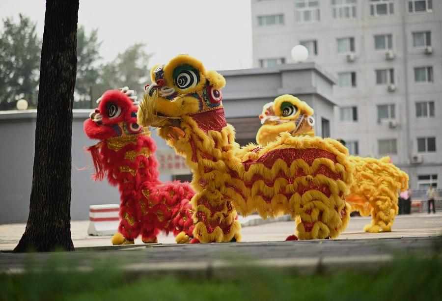 Lion dancers perform along a street in Beijing, China, on 6 July 2021. (Noel Celis/AFP)