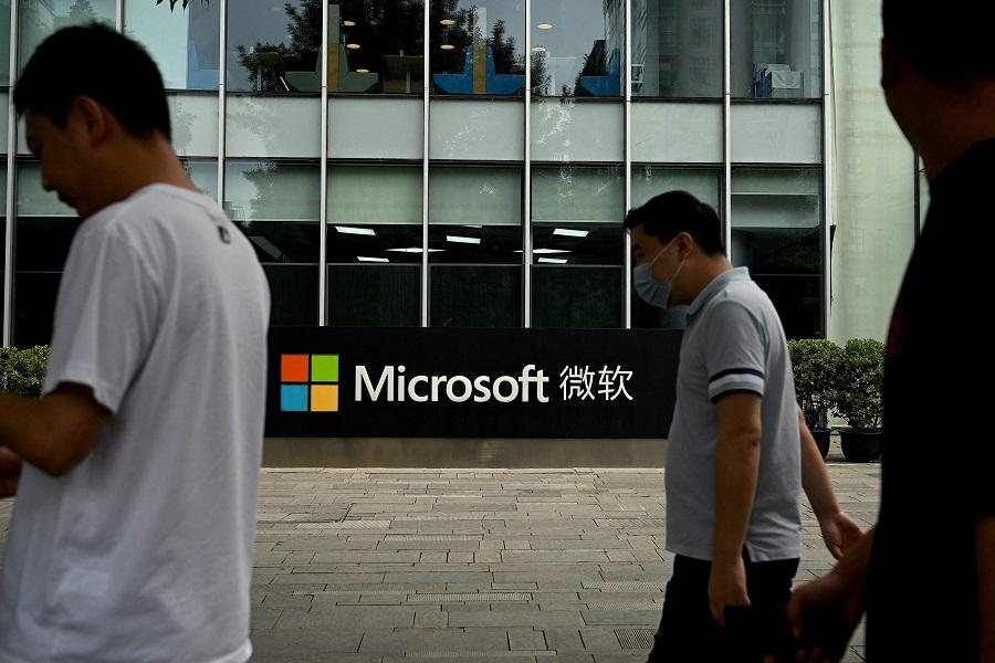 Pedestrians walk past Microsoft's local headquarters in Beijing, China, on 20 July 2021. (Noel Celis/AFP)