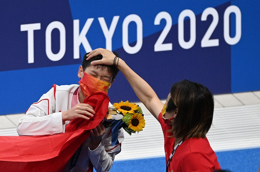 Gold medalist Quan Hongchan has her hair ruffled by a member of the coaching staff as she leaves the pool after winning the women's 10m platform diving final event during the Tokyo 2020 Olympic Games at the Tokyo Aquatics Centre in Tokyo, Japan, on 5 August 2021. (Oli Scarff/AFP)