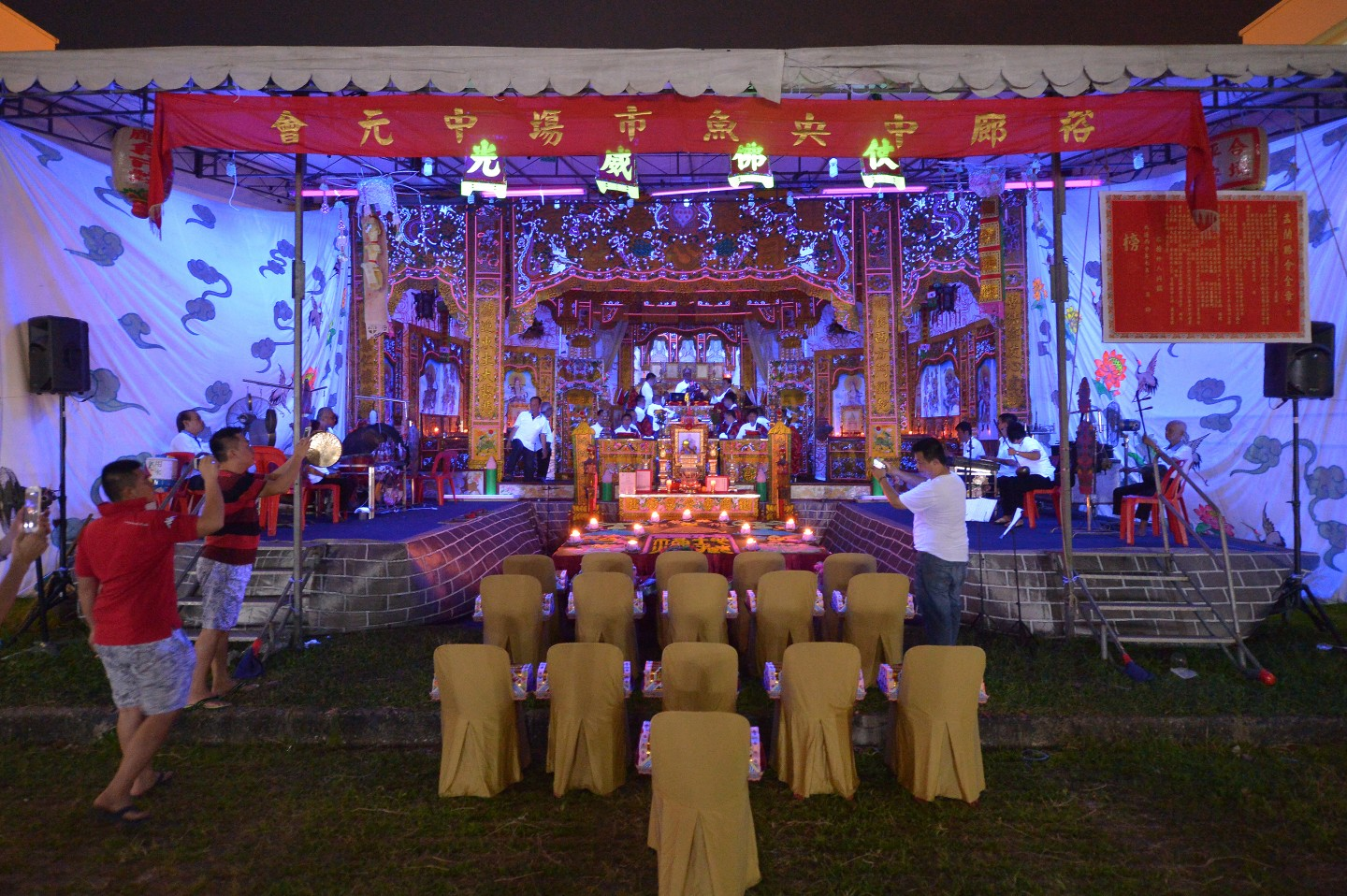 Prayers and rituals are conducted on stage, behind a feast that has been laid for the spirits during the Hungry Ghost Festival at Jurong Fishery Port on 18 August 2016. Food offerings are seen as a way of appeasing wandering spirits, while prayers help relieve them of suffering. Seats near the stage have been left empty for the spirits. (SPH)