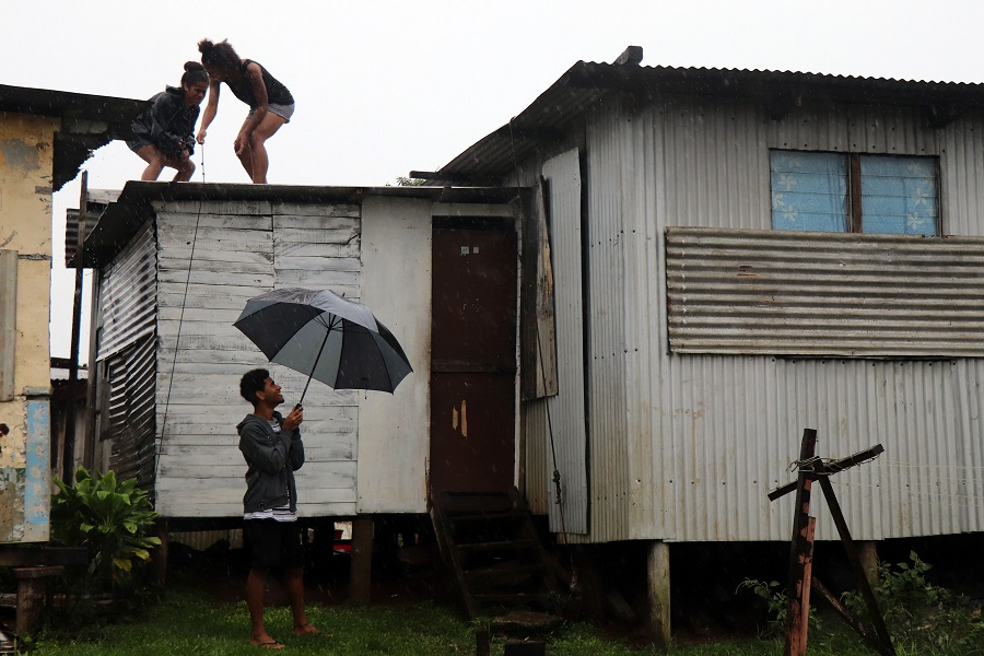 This picture taken on 17 December 2020 shows residents checking the rooftops of their houses as gusty winds build up ahead of cyclone Yasa in Fiji's capital city of Suva. (Lice Movono/AFP)