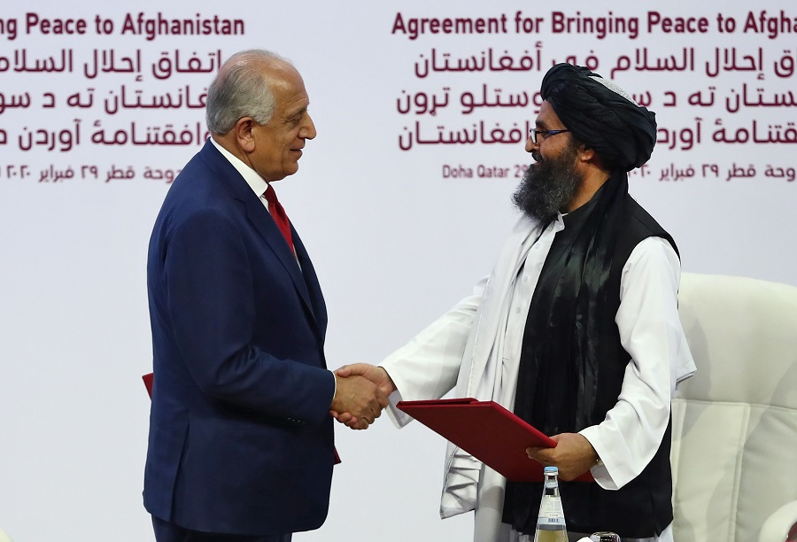 In this file photo taken on 29 February 2020, US Special Representative for Afghanistan Reconciliation Zalmay Khalilzad (right) and Taliban co-founder Mullah Abdul Ghani Baradar shake hands after signing a peace agreement during a ceremony in Doha. (Karim Jaafar/AFP)