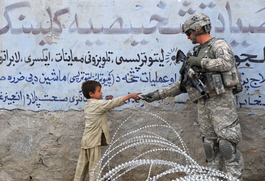 In this file photo taken on 20 February 2010, a US soldier from 4th Infantry Division 4 Brigade Alpha Company presents a gift to an Afghan child during a patrol at Khogiani in Nangarhar, Afghanistan. (Kim Jae-hwan/AFP)