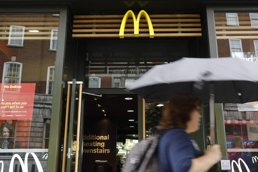 In this file photo taken on 4 September 2017, a woman walks past a McDonald's branch in central London, UK. (Tolga Akmen/AFP)
