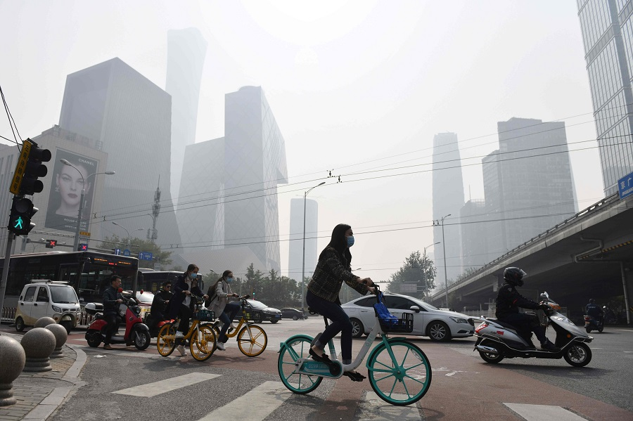 This file photo taken on 10 October 2020 shows people crossing a road on a polluted day in Beijing, China. (Greg Baker/AFP)