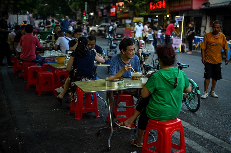 This file photo taken on 5 August 2020 shows people eating during the afternoon in front of a small restaurant in Wuhan, Hubei, China. (Hector Retamal/AFP)