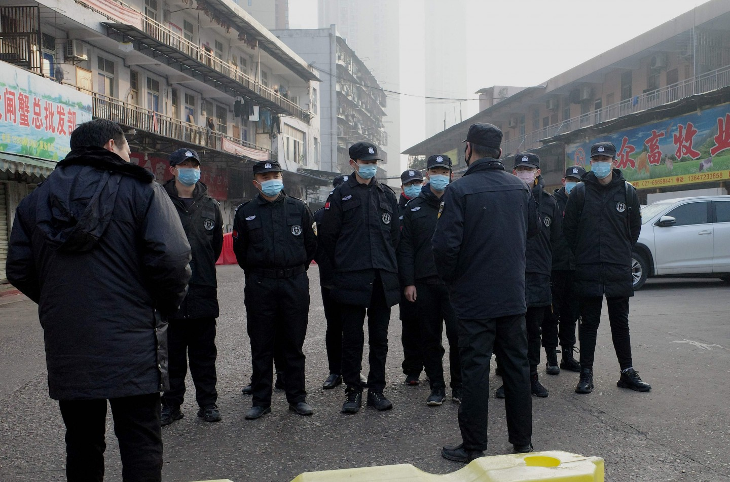 In this file photograph taken on 11 January 2020 security guards stand in front of the closed Huanan wholesale seafood market, where health authorities say a man who died from a respiratory illness had purchased goods from. (Noel Celis/AFP)