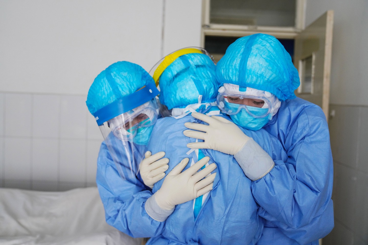 This file photo taken on 28 January 2020 shows medical staff members hugging each other in an isolation ward at a hospital in Zouping in China's easter Shandong province. (STR/AFP)