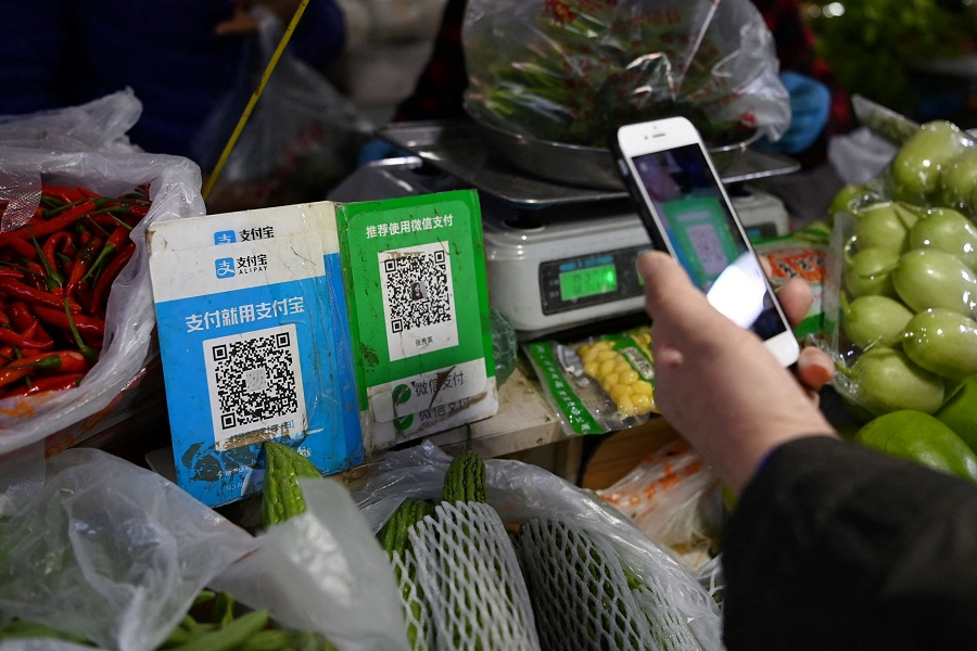 This file photo taken on 3 November 2020 shows a customer making a payment using a Wechat QR payment code (centre) via her smartphone, next to an Alipay QR code (left), at a vegetable market in Beijing, China. (Greg Baker/AFP)
