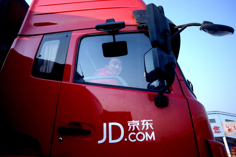 This file photo taken on 3 November 2015 shows a driver for online marketplace JD.com smiling as he sits in his truck outside the company's warehouse in Langfang, Hebei province, China. (Wang Zhao/AFP)